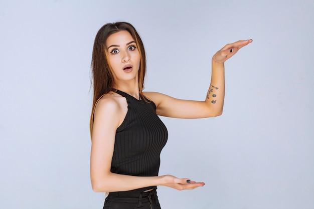 Kobieta w czarnej koszuli przedstawiająca miarę obiektu.
