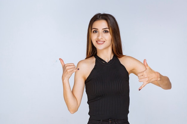 Kobieta w czarnej koszuli robi znak wywoławczy.
