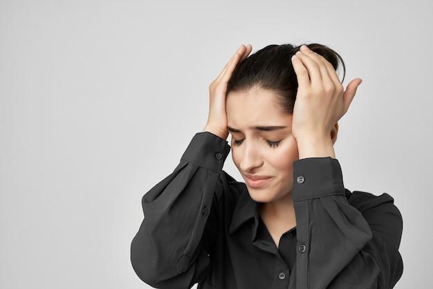 Kobieta w czarnej koszuli trzymająca głowę przygnębiona problemami zdrowotnymi