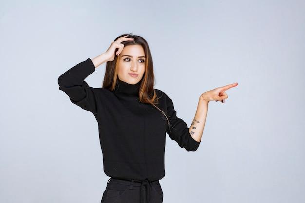 Kobieta w czarnej koszuli wskazując coś po prawej stronie.