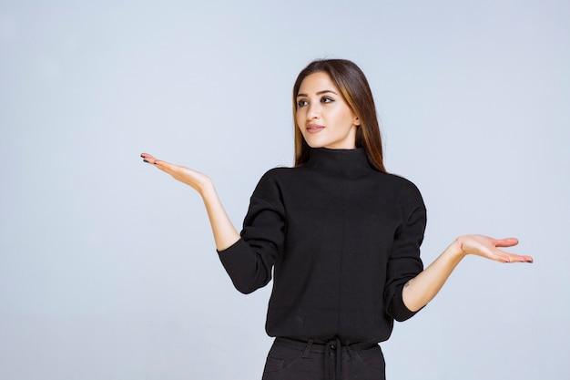 Kobieta w czarnej koszuli, wskazując na coś po lewej stronie.