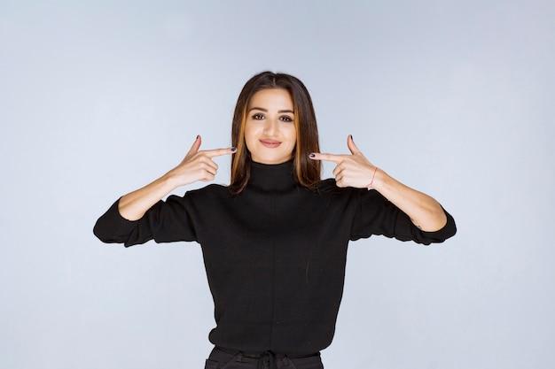 Kobieta w czarnej koszuli, wskazując na jej uśmiech.