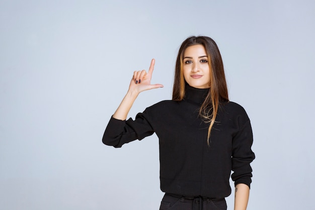 Kobieta w czarnej koszuli, wskazując powyżej.