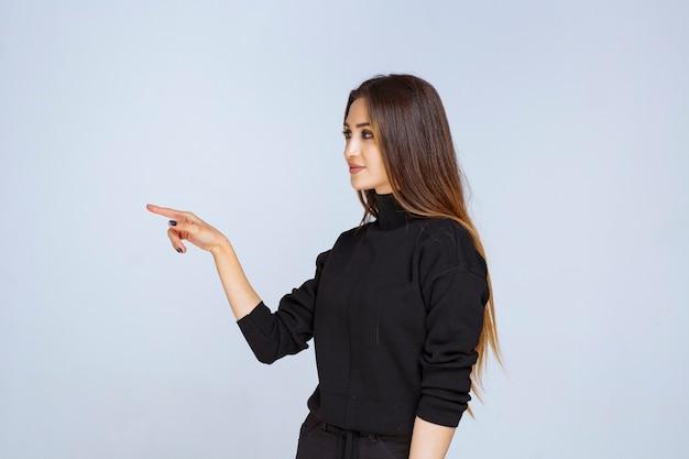 Kobieta w czarnej koszuli, wskazując w lewo i pokazując jej emocje.
