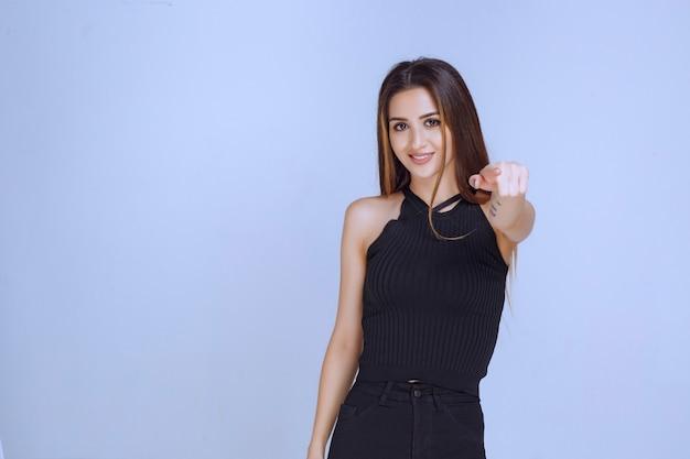 Kobieta w czarnej koszuli wskazując widza przed sceną.