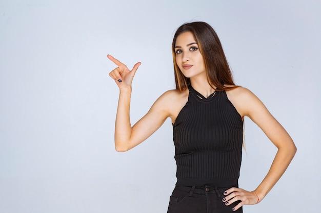 Kobieta w czarnej koszuli wskazuje gdzieś palcem.
