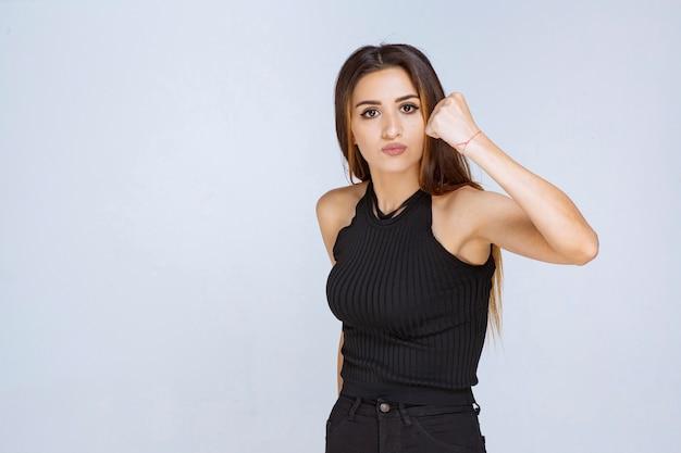 Kobieta w czarnej koszuli wygląda agresywnie i zdenerwowana.