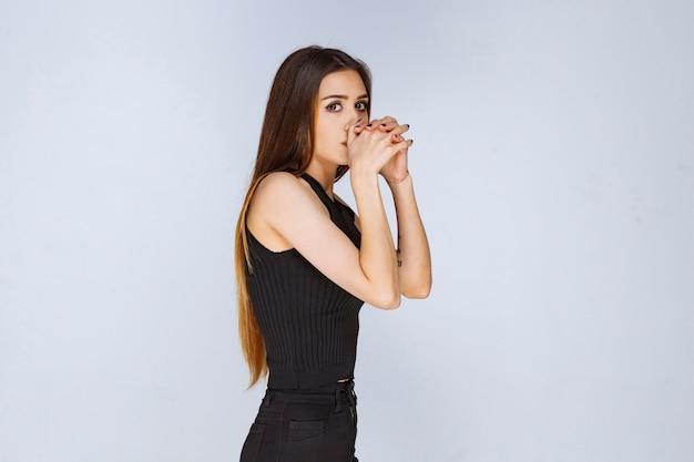 Kobieta w czarnej koszuli wygląda tajemniczo.