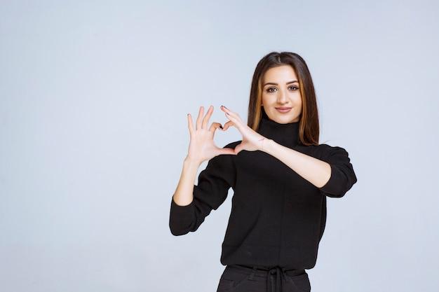 Kobieta w czarnej koszuli wysyłająca miłość do swojego partnera.