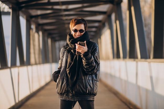 Kobieta w czarnej kurtce idąc przez most