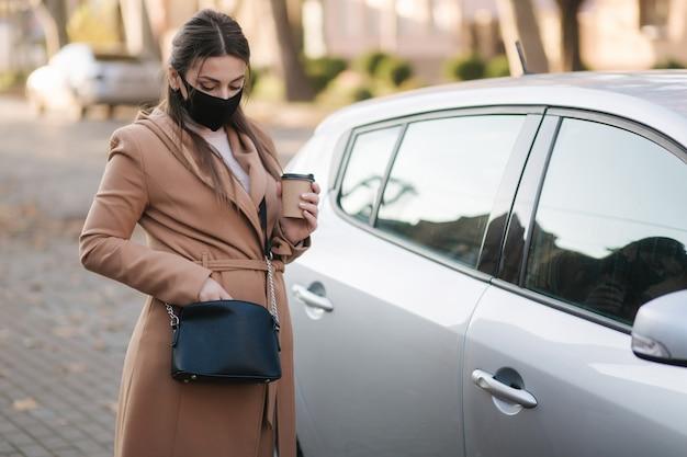 Kobieta w czarnej masce trzyma kawę przy samochodzie i patrzy na kluczyk.