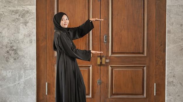 Kobieta w czarnej muzułmańskiej sukience wskazująca tępo na bok przed drzwiami