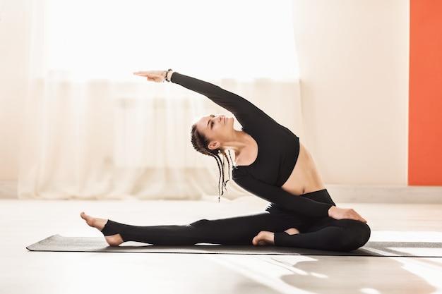 Kobieta w czarnej odzieży sportowej uprawia jogę, robi uproszczone ćwiczenie parivritta janu shirsasana