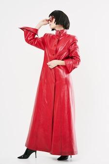 Kobieta w czarnej peruce i czerwonej kurtce na białym tle