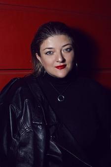 Kobieta w czarnej skórzanej kurtce na czerwonej ścianie