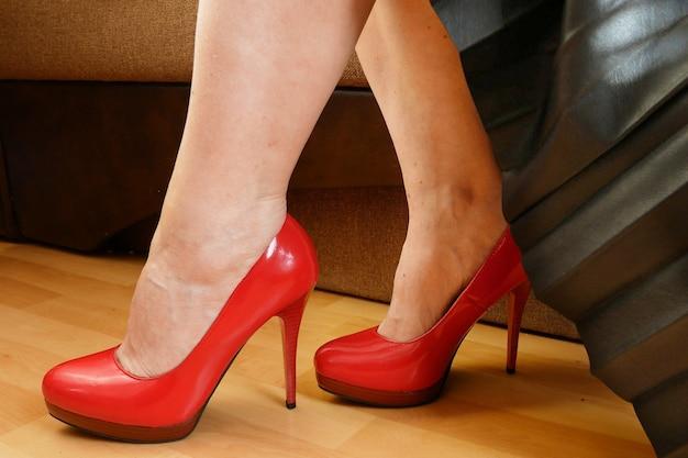Kobieta w czarnej skórzanej spódnicy i czerwonych butach na wysokim wzgórzu, zbliżenie