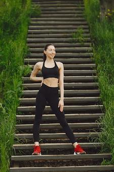 Kobieta w czarnej spoerswear stojąca na schodach
