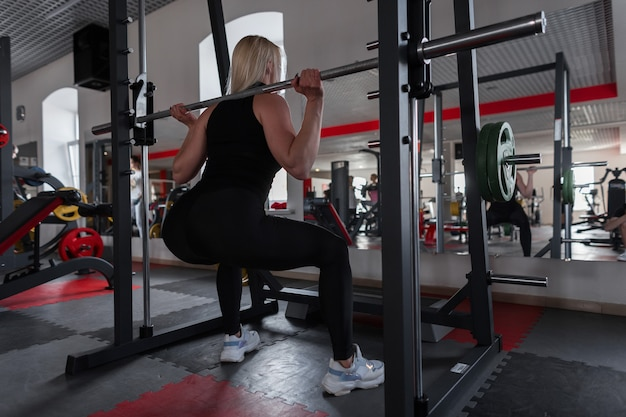 Kobieta w czarnej stylowej odzieży sportowej w trampkach kuca z metalowym sępem na ramionach w pomieszczeniu