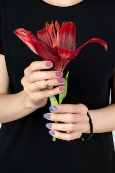 Kobieta w czarnej sukience trzyma bordową lilię