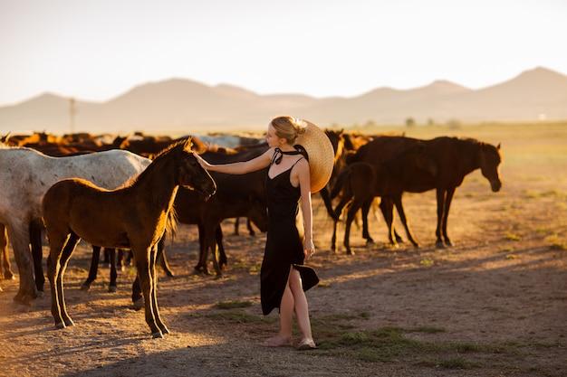 Kobieta w czarnej sukience wśród dzikich koni