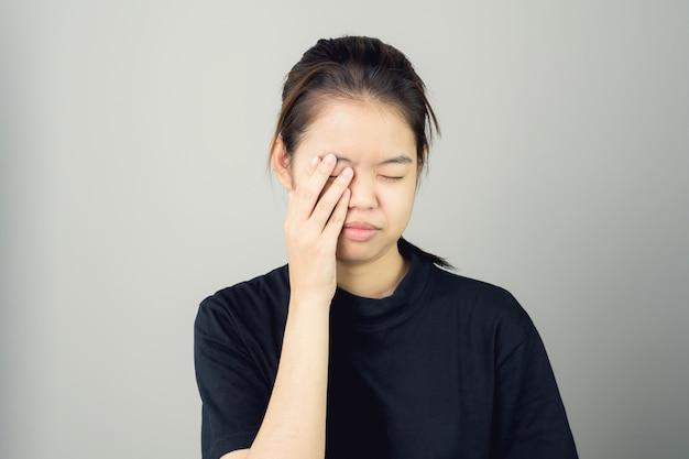 Kobieta w czarnej sukni dotyka głowy, aby pokazać jej ból głowy.