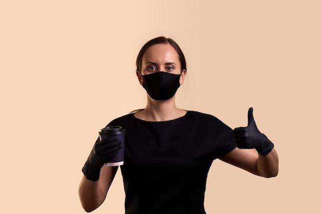 Kobieta w czarnej sukni maska i rękawiczki lateksowe trzymając gorący napój w jednorazowym kubku i pokazując kciuk do góry na beżowej ścianie