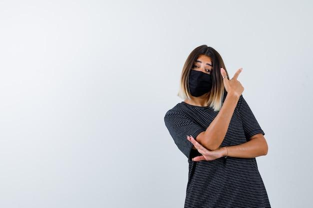 Kobieta w czarnej sukni, maska medyczna skierowana w prawy górny róg i wyglądająca niepewnie, widok z przodu.