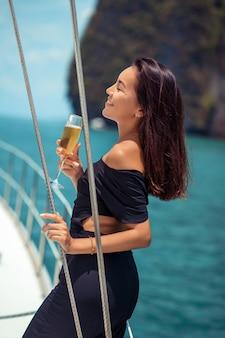Kobieta w czarnej sukni pije szampana na pokładzie jachtu