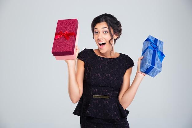 Kobieta w czarnej sukni trzyma dwa pudełka na prezenty