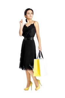 Kobieta w czarnej sukni z torby na zakupy na białym tle.