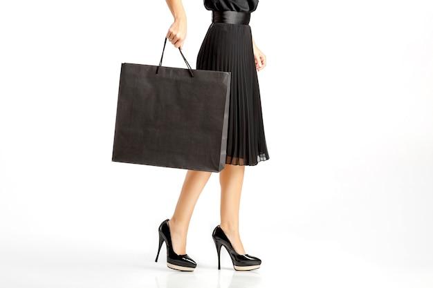 Kobieta w czarnej sukni z torby na zakupy