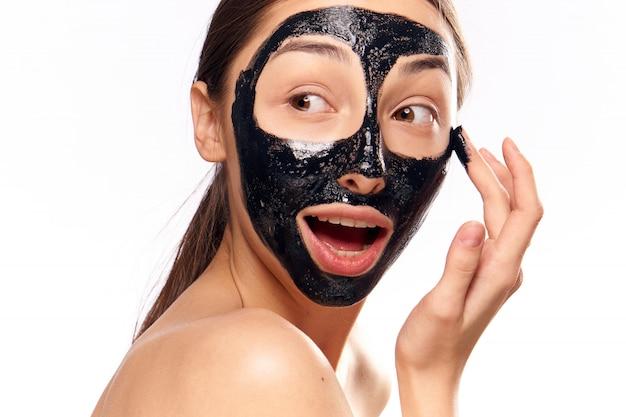 Kobieta w czarnej twarzy maski oczyszczającej