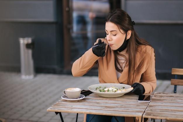 Kobieta w czarnych rękawiczkach trzyma sztućce. koncepcja quarantine cafe. jedzenie na zewnątrz w rękawicach ochronnych.