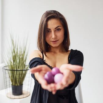 Kobieta w czarnych seksownych ubraniach pokazuje w pokoju kulki dopochwowe i narzędzia do budowania.