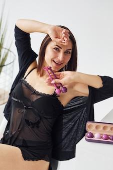 Kobieta w czarnych seksownych ubraniach, z kulkami dopochwowymi i narzędziami do budowania w pokoju.