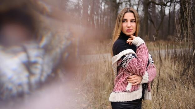 Kobieta w czarnych spodniach i ciepłym swetrze stojącym na polu suszonych kłosków