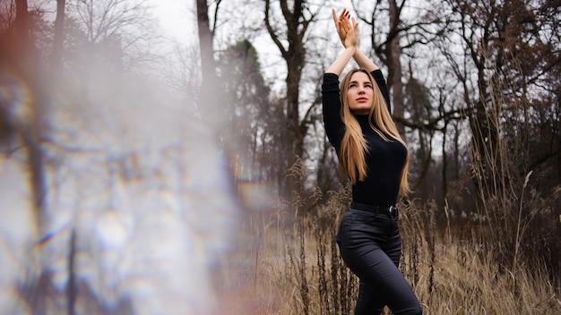 Kobieta w czarnych spodniach i swetrze stojących na polu suszonych kłosków ręce do góry