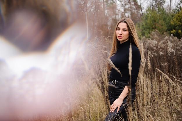 Kobieta w czarnych spodniach i swetrze stojących na polu suszonych kłosków