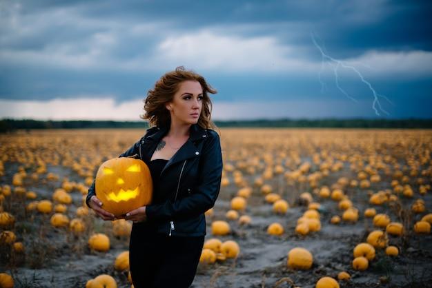 Kobieta w czarnych ubraniach trzyma dynię w dłoniach, koncepcja halloween