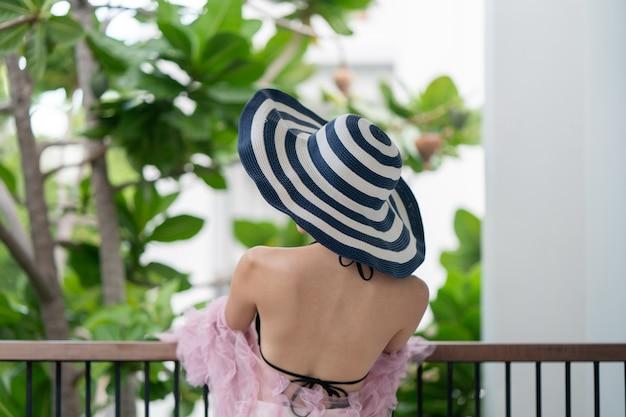 Kobieta w czarnym bikini obejmujące twarz kapeluszem.