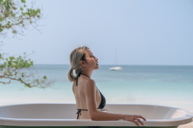 Kobieta w czarnym bikini relaks w wannie z plaży oceanu.