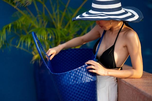 Kobieta w czarnym bikini zakrywająca twarz kapeluszem, szukająca czegoś w torebce.