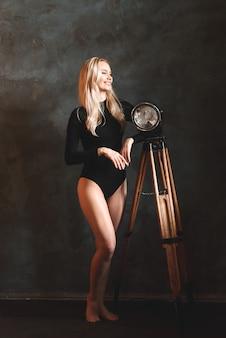 Kobieta w czarnym body. dziewczyna z falowanymi włosami. zmysłowa wspaniała młoda dama w czarnym body pozuje w studio