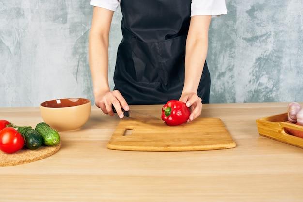 Kobieta w czarnym fartuchu na deskę do krojenia warzyw w kuchni. zdjęcie wysokiej jakości