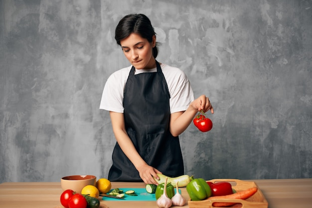 Kobieta w czarnym fartuchu obiad w domu deska do krojenia wegetariańskich potraw