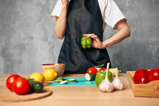 Kobieta w czarnym fartuchu obiad w domu dieta wegetariańska