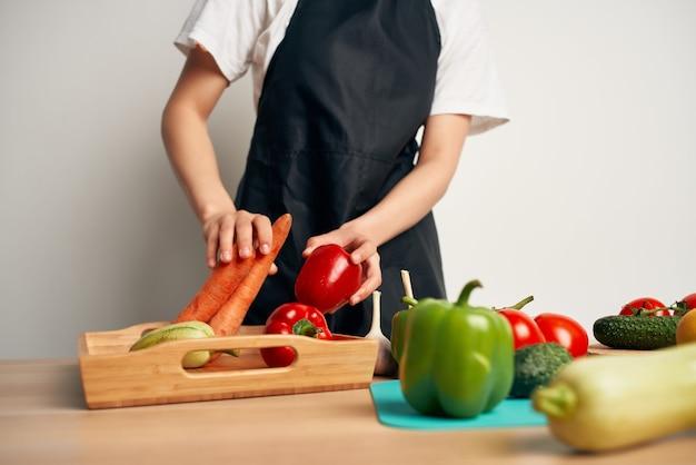 Kobieta w czarnym fartuchu w kuchni kroi dietę warzywną