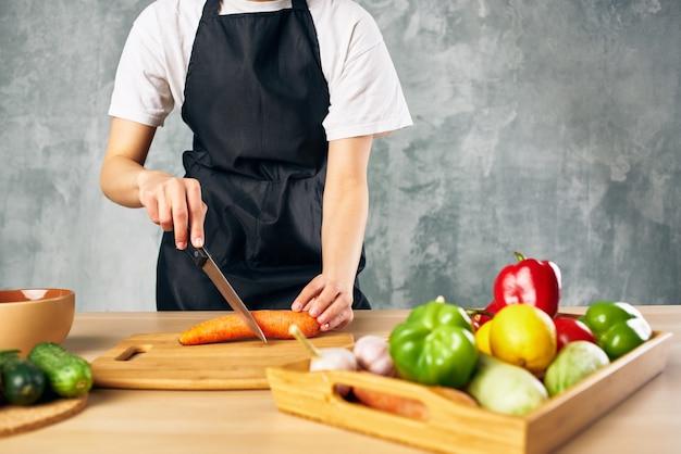 Kobieta w czarnym fartuchu w kuchni kroi warzywa gotuje sałatkę witaminy