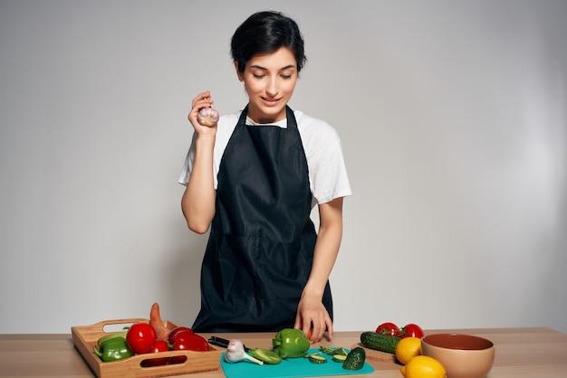 Kobieta w czarnym fartuchu w kuchni warzywa świeże witaminy żywności