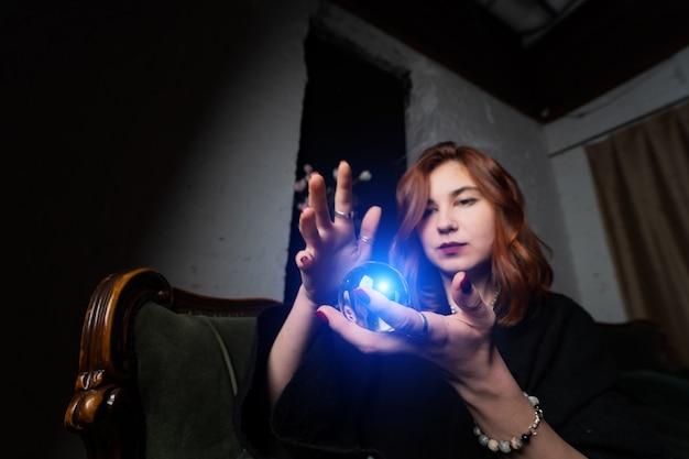 Kobieta w czarnym garniturze gospodarstwa kryształowej kuli